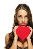 Gorgeous brunette woman holding red heart — Stockfoto
