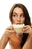 Beautiful woman drinking cappuccino coffee looking to side — Stock Photo