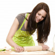 Young woman using rolling pin on dough — Stock Photo #11129980