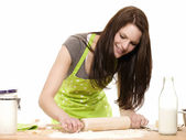 Young woman using rolling pin on dough — Stock Photo