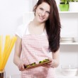 Woman in a kitchen adding sliced paprika to her salad — Stock Photo #11292014