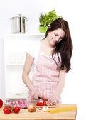 Happy woman cutting tomatoes — Stock Photo