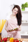 Woman in a kitchen adding sliced paprika to her salad — Stock Photo