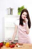 Young woman eating tomato — Stockfoto