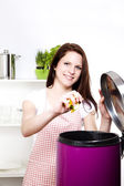 Woman throwing some waste in a trash can — Stockfoto