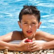 Boy eating fruit in swimming pool — Foto de Stock