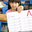 Stock Photo: Smiling little girl showing exam paper with a plus in the classroom