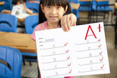 Smiling little girl showing exam paper with a plus in the classroom — Stock Photo