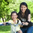 Asian mother Teaching daughter To Ride A bicycle — Stock Photo