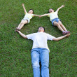 Happy asian family lying and playing on the grass — Stock Photo