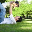 Stock Photo: Happy father and little girl on the grass