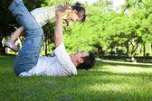 Szczęśliwy ojciec i mała dziewczynka na trawie — Zdjęcie stockowe