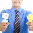 Smiling businessman holding energy saving light bulb and tradition light bulb — Stock Photo