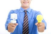 Usměvavý obchodník drží energeticky úsporné žárovky a žárovky tradice — Stock fotografie