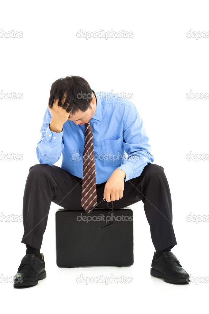 Frustrated businessman sitting on the briefcase  Stock Photo #11153932