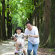 Father Teaching daughter to riding bicycle — Stock Photo #11371111