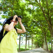 Young woman with backpack standing in the green forest taking photo — Stockfoto
