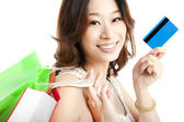 Happy woman with shopping bag and credit card — Стоковое фото