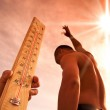 Man throwing water for cooling temperature and hand holding thermometer under heat weather — Stock Photo