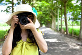 Young traveler taking photo in the green forest — Stock Photo
