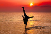 Young man hand stand on the beach at sunset — Stok fotoğraf