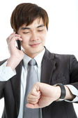 Asian businessman checking time while talking on mobile phone — Stock Photo