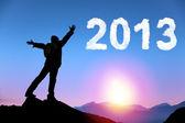 ευτυχισμένο το νέο έτος 2013. νέος άνθρωπος στέκεται στην κορυφή βουνού, βλέποντας την ανατολή του ηλίου και σύννεφο 2013 — Φωτογραφία Αρχείου