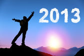 Happy new year 2013. young man standing on the top of mountain watching the sunrise and cloud 2013 — ストック写真