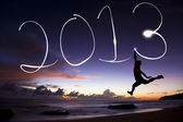 Happy new year 2013. young man jumping and drawing 2013 by flashlight in the air on the beach before sunrise — Stock Photo