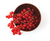 Röda vinbär i en trä kopp på en vit bakgrund — Stockfoto