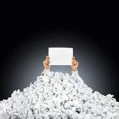Person under skrynkliga hög av papper med handen håller en hjälp si — Stockfoto