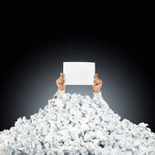Person under crumpled pile of papers with hand holding a help si — Stock Photo