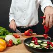 Chef adding ingredients — Stock Photo