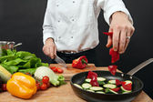 Chef adding ingredients — Stock Photo