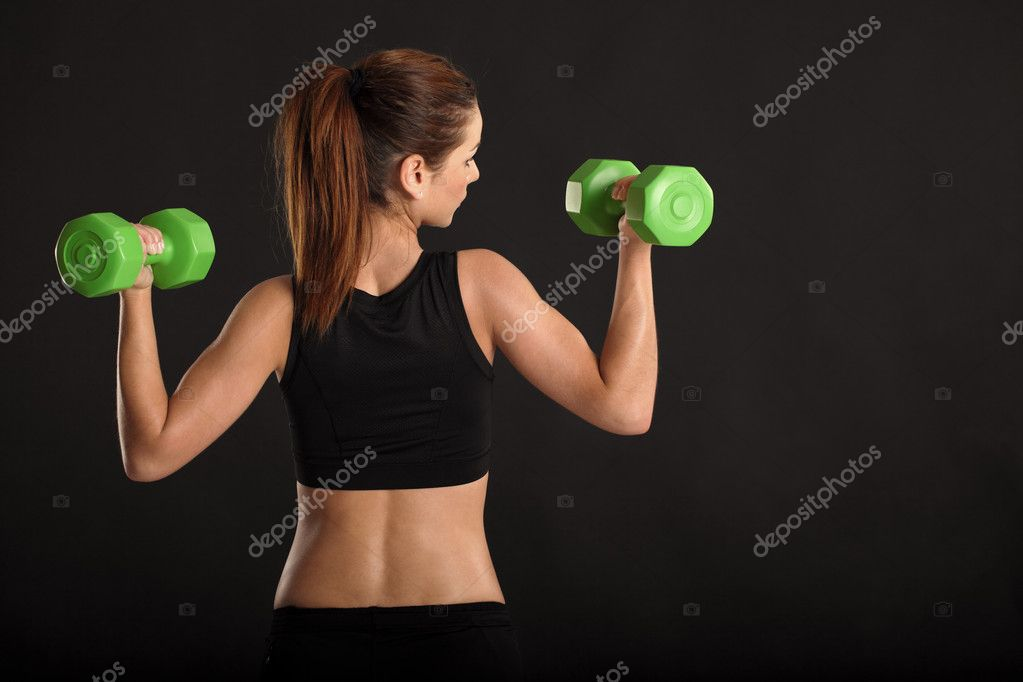 Photo of a toned young female exercising with dumbbells.  Foto de Stock   #11741227