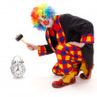 Clown hitting alarm clock with hammer — Stock Photo