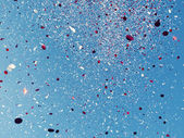 Red and White confetti against a blue sky — Stock Photo