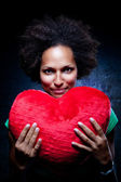 Afroamerican Woman with a Heart-Shaped Cushion — Stock Photo