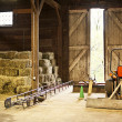 Stock Photo: Barn interior with hay bales and farm equipment