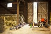 Intérieur de la grange avec des balles de foin et de matériel agricole — Photo