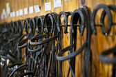 Horse bridles hanging in stable — Stock Photo
