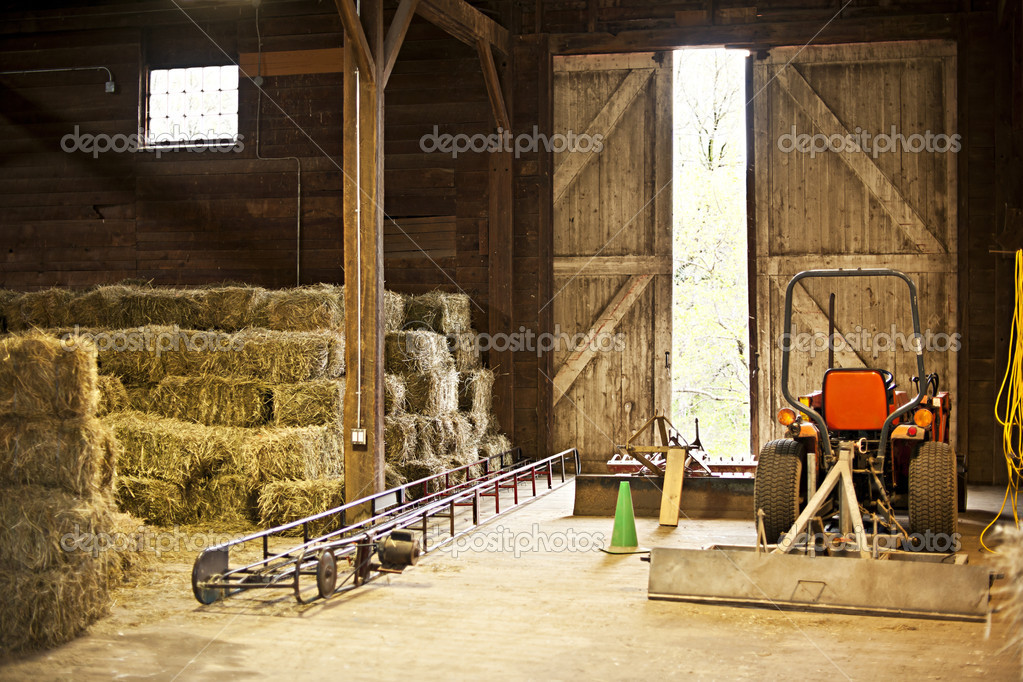 Interior of wooden barn with hay bales stacks and farm equipment  Stock Photo #11551137