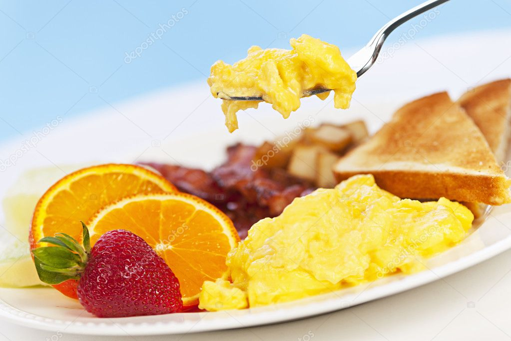 Scrambled eggs on a fork above breakfast plate with fruits toast and bacon — Stock Photo #11551156