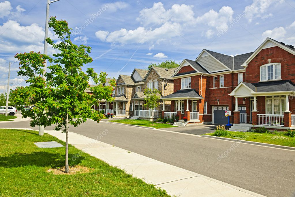 Suburban residential street with red brick houses  Stock Photo #11551405
