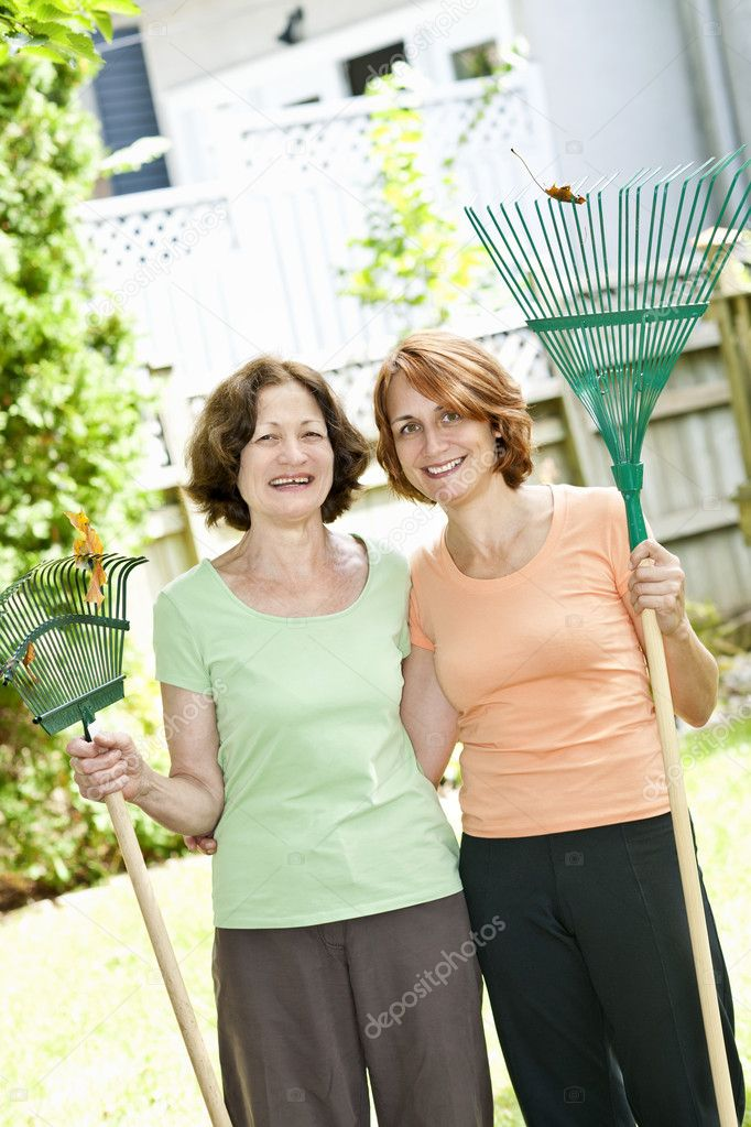 Mother and daughter holding rakes gardening outside — Stock Photo #11552019