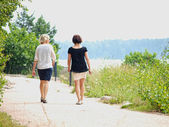 Couple of women walking while talking on a gravel road at summer — Stock Photo