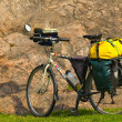 Loaded touring bicycle on rest break, next to mauntain — Stock Photo #11646600