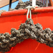 Close-up of an old frayed boat rope, on a red boat — Stock Photo