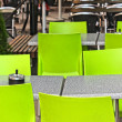 Foto de Stock  : Restaurant outdoors with green chairs, nobody around