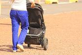Parent having a walk with a kid stroller, on tile floor in the city — ストック写真
